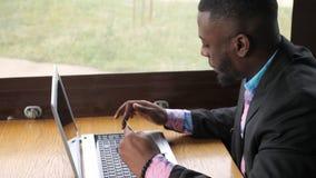Svarta mannen gör betalningkontokortet på bärbara datorn köper direktanslutet och att shoppa sitter i kafé stock video