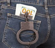 Svarta metallhandbojor och amerikansk valuta i jeans stoppa i fickan Royaltyfri Bild