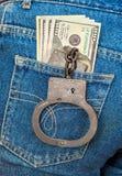 Svarta metallhandbojor och amerikansk valuta i jeans stoppa i fickan Fotografering för Bildbyråer