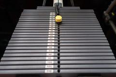 Svarta metalliska eller för järn tunga plattor som staplas för sport, övning, viktmaskin med kg och pundnummer i konditionidrotts Royaltyfri Foto