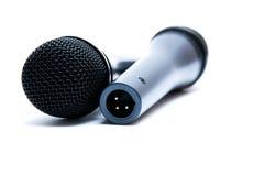 Svarta mikrofoner på en vit bakgrund Arkivfoto