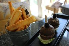 Svarta nötkötthamburgare med Chunky French Fries Royaltyfri Bild
