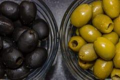 Svarta och gröna oliv i glass bunkar på mörk bakgrund Royaltyfri Bild