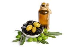 Svarta och gröna oliv som är blandade i porslinbunken och oskuldolivoljan arkivfoton