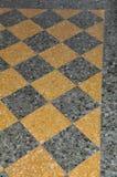 Svarta och gula golvtegelplattor i hus Arkivbilder