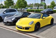 Svarta och gula Porsche 911 Carrera 4 GTS Arkivfoto
