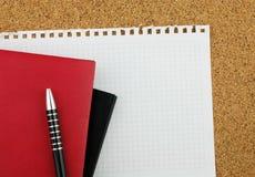 Svarta och röda anteckningsböcker på det rena vita arket med den svarta pennan på korken stiger ombord bakgrund Royaltyfri Foto