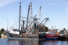 Svarta och röda fiskebåtar Arkivbild