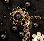 Svarta pärlor för makro i guld- blommor för metall Royaltyfria Foton