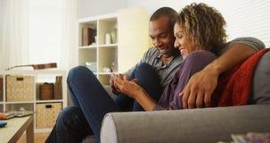 Svarta par genom att använda smartphonen tillsammans på soffan Royaltyfri Bild