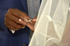 Svarta par som utbyter vigselringar Royaltyfria Bilder