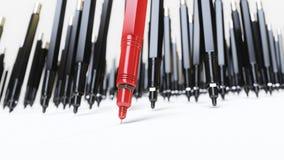 Svarta pennor Finepoint för mekanisk teckning som drar perfekta linjer på en vit yttersida som ledas av en röd penna stock illustrationer