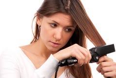 svarta plana hårjärnstraighteners som använder kvinnan Arkivbild