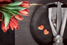 Svarta plattor, svarta servetter, tappningbestick med röda tulpan och Royaltyfria Foton