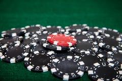 Svarta pokerchiper med en som är röd Arkivbild