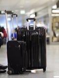 Svarta resväskor som står flygplatsen Royaltyfria Bilder