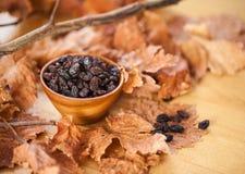 Svarta russin i en träbunke På det torra bladet och brun träbac Arkivbilder