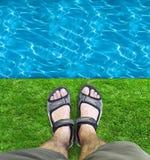 Svarta sandaler på gräset Arkivbild