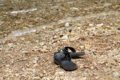 Svarta sandaler sätts ner på flodstranden Royaltyfri Bild
