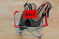 Svarta skor för hög häl för sammet för damer inom mini- shoppingvar Royaltyfria Foton