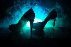 Svarta skor för kvinnor för hög häl för mockaskinn på mörker tonade dimmig bakgrund close upp Kvinnor driver eller kvinnadominans Royaltyfri Bild