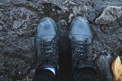 Svarta skor i gyttjan ovanför sikt royaltyfria bilder