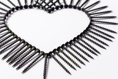 Svarta skruvar som läggas ut i formen av en hjärta på en vit bakgrund royaltyfri bild