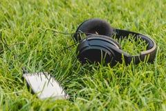 Svarta Smartphone och hörlurar på det gröna gräset Arkivbilder