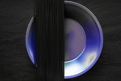Svarta spagettinudlar på lilaplattan som förlade på svart stenyttersida Royaltyfria Foton