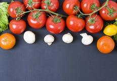 svarta tomater för bakgrund dietary mat svarta morotgrönsaker för bakgrund Tomater på tabellen Arkivbilder