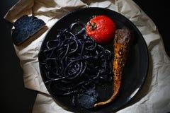 Svarta udonnudlar, pasta med tioarmad bläckfiskfärgpulver, tomat och morot Royaltyfria Bilder
