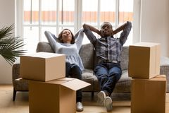 Svarta unga par att koppla av på soffan som är trött på rörande dag royaltyfri fotografi