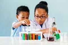 Svarta ungar som gör kemiexperiment royaltyfri bild