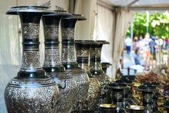 Svarta vaser med förgyllda prydnader i en gata shoppar royaltyfria foton