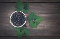 Svarta vinbär överhopar closeupen på lantlig wood bakgrund Royaltyfri Fotografi