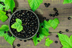 Svarta vinbär med gröna sidor i krukmakerileran bowlar på en träbakgrund Royaltyfri Foto
