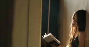 Svartdamunderkläder för kvinna n sitter på golvet som läser en bok Hem- inomhus, aftonljus 4K stock video
