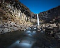 Svartifoss i Island med regnbågemiddagar inga moln Arkivbild