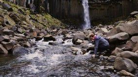 Woman near Svartifoss waterfall in Skaftafell National Park. Svartifoss waterfall in Skaftafell National Park stock footage