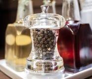 Svartpeppar i den glass grinderbehållaren Fotografering för Bildbyråer