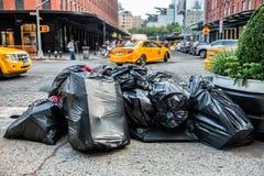 Svartpåsar av avfall på trottoaren i den New York City gatan som väntar på den tjänste- avfalllastbilen Avskräde som packas i sto Arkivfoton