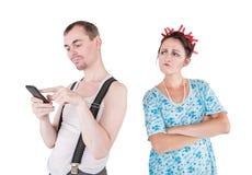 Svartsjuk fru som h?ller ?gonen p? hennes make som anv?nder mobiltelefonen royaltyfri fotografi
