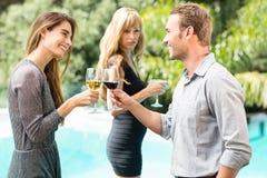 Svartsjuk kvinna som ser lyckliga par som rostar vin Arkivbilder