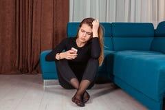 Svartsjuk kvinna som sitter på appell för känsla för golvinnehavtelefon ledsen väntande på fotografering för bildbyråer