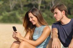 Svartsjuk pojkvän som håller ögonen på hans flickvän smsa på telefonen Arkivfoton