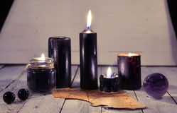 Svartstearinljus, gammalt pergament och magisk boll mot vit plankabakgrund Royaltyfri Fotografi