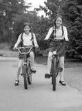 Svartvit bild av att le flickor som rider cyklar till skolan Arkivbild