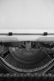 Svartvit bild av den antika skrivmaskinen och tomt papper Fotografering för Bildbyråer