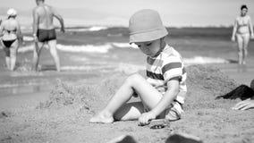 Svartvit bild av den gulliga litet barnpojken i hatten som sitter på havsstranden och spelar med leksakbilar Barn som kopplar av  royaltyfria bilder