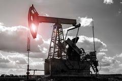 Svartvit bild av en olje- borrtorn med en ljus röd ilsken blick arkivbild